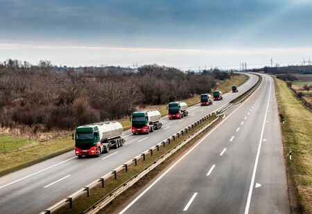 Convoy or Caravan of Tank trucks on a winding Highway through the rural landscape