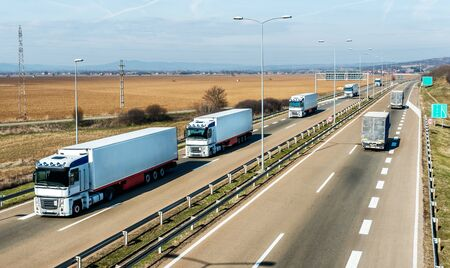 Convoy of White transportation  trucks in line as a caravan or convoy on a countryside highway under a blue sky