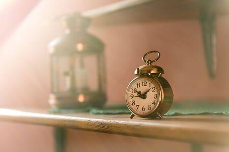 Vintage alarm clock on a shelf lit by morning sun rays. Vintage background items. Imagens