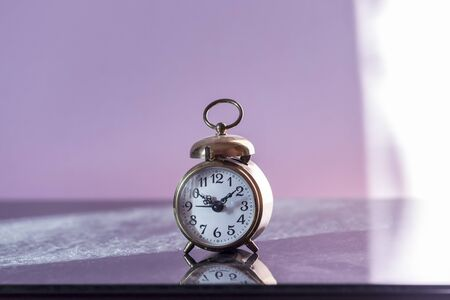 Vintage alarm clock on a dusty Cupboard lit by morning sun rays. Vintage backgrounds