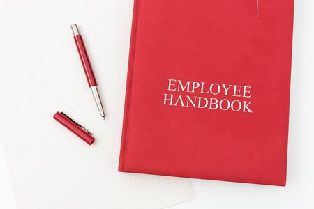 Employee Handbook or manual with a pen and paper on a white table in an office - personnel management policy, explains business goals, results, defines personnel practices Stock Photo