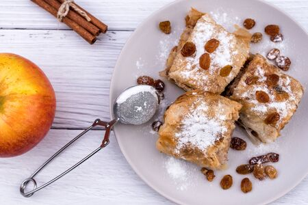 Slices of homemade Apple pie strudel in a plate with ingredients on a rustic white wooden table. Pie with apples, raisins and cinnamon, sweet pastries - Top View