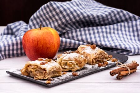 Slices of homemade Apple pie strudel in a plate with ingredients on a rustic white wooden table. Pie with apples, raisins and cinnamon, sweet pastries
