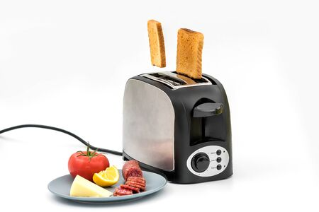 Toasts jumping out of retro style black and metallic toaster on white background. Levitation food. Kitchen equipment for fresh morning meal with sandwich ingredients - tomato, cheese, dried sausage.
