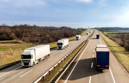 Transport autostradą z konwojem ciężarówek mijających ciężarówki pod pięknym niebem o zachodzie słońca