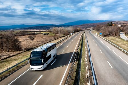 White Modern comfortable tourist bus driving through highway at bright sunny sunset. Travel and coach tourism concept. Trip and journey by vehicle Stock Photo
