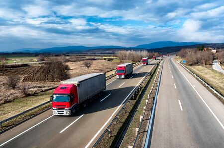Fleet of Red Trucks in line as a convoy at a rural countryside highway under a beautiful blue sky Stock Photo - 147727876