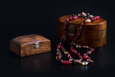 Two Old wooden jewelry caskets and a glass bead necklace isolated on black background. Wooden boxes for different decorations or small trifles. Stock Photo