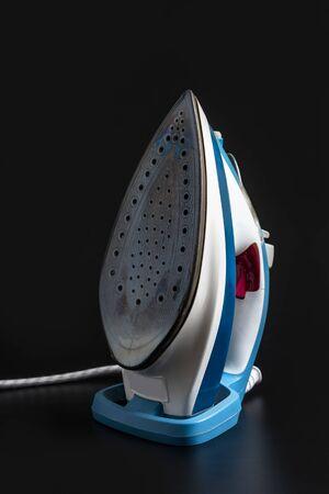 Well used Steam iron isolated on Black background. Electronic ironing. Standard-Bild