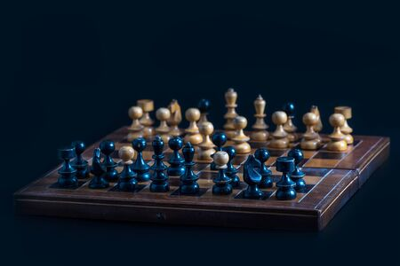 Old chess figures on a wooden board. Occupation on vacation and recreation - old chess set. Stock Photo