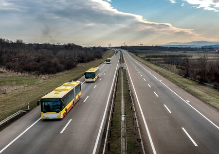 Intercity Yellow Line Buses in line traveling on a rural country highway. Bus passenger transportation concept.