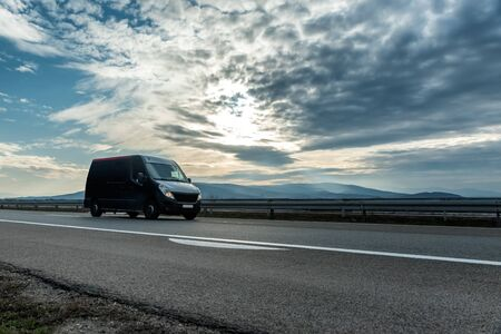 Delivery van on the highway road at sunset. Transports, logistics concept Stock Photo