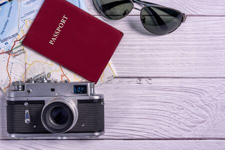 Top view traveler accessories on wooden background. Flat lay vintage camera, sunglasses, map  and passport document. Travel planning concept