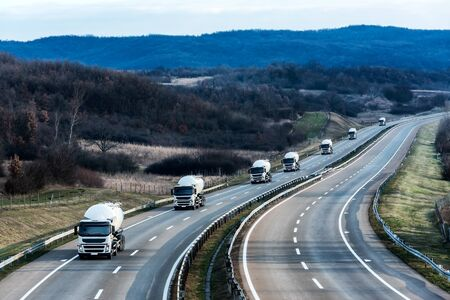 Fleet of White Tank truck or cistern as a convoy on a Highway through the rural landscape. Business Transportation And Trucking Industry.