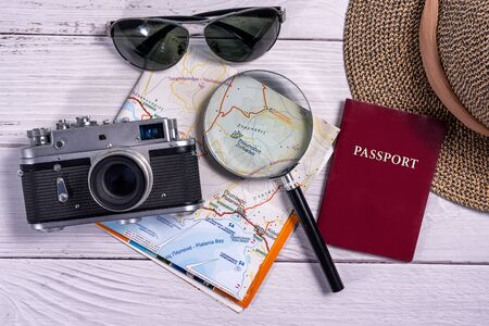 Top view traveler accessories on wooden background. Flat lay vintage camera, sunglasses, map, magnifying glass, straw hat and passport document. Travel planning concept Stock Photo