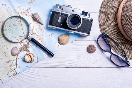 Top view of planning vacation planning using a map, magnifier, retro camera - Travel influencer looking for the next travel destination - Concept of adventure, tourism, and traveling people lifestyle Stock Photo