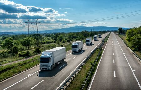 Fleet of light blue transportation  trucks in line as a caravan or convoy on a country highway under an amazing blue sky. Business Transportation And Trucking Industry. Stock Photo