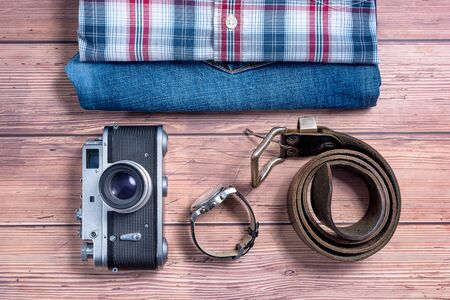 Tourism concept - Vintage camera, jeans, shirt, belt and wrist watch on wooden table background Stock Photo