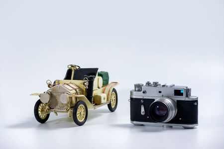 Tourism and travel concept - Vintage camera and tin vintage car model on a white background Stock Photo