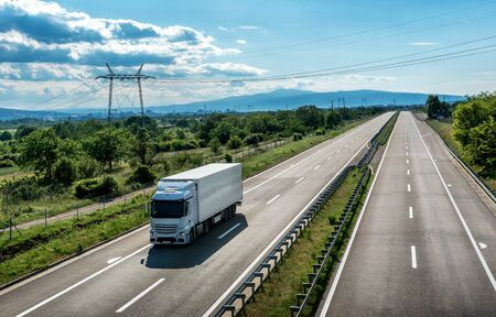 Light Blue Transportation Truck on a four lane Highway through the rural landscape with a beautiful blue sky and soft clouds Stock Photo