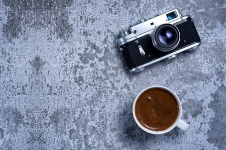 Vintage Travel camera and coffee cup on an old rustic table. Top view with copy space