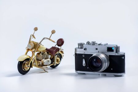 Tourism and travel concept - Vintage camera and tin vintage motorcycle model on a white background Stock Photo