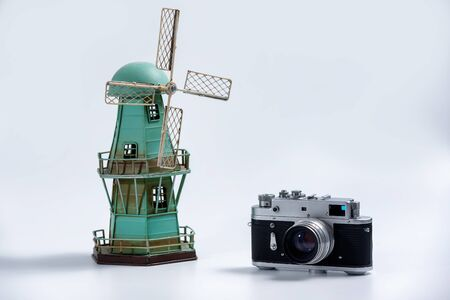 Tourism and travel concept - Vintage camera and tin vintage windmill model on a white background