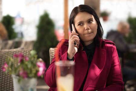 Image of a beautiful adult woman wearing a pink coat talking on a cellphone while sitting in street cafe restaurant outdoors