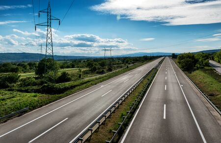Empty silent Asphalt highway road with beautiful sky and a row of electricity pylons Stock Photo