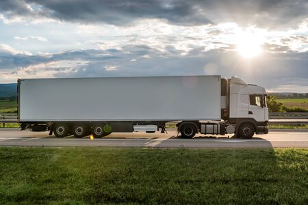 White truck is on highway - business, commercial, cargo transportation concept, beautiful sunset sky, clear and blank space - side view Stock Photo