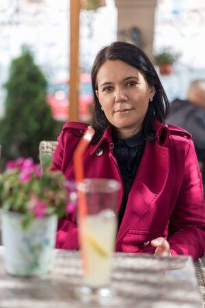 Image of smiling beautiful adult woman in wearing a pink coat sitting in street cafe restaurant outdoors Stock Photo - 150064387