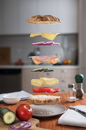 Levitating Sandwich with its ingredients. Deconstructed sandwich layers in kitchen Stock Photo