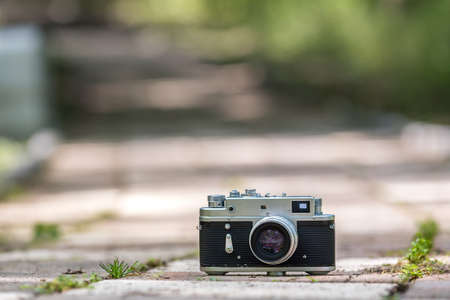 Spring time mood still life: vintage rangefinder camera laying on pavement with leaves of grass growing through, selective focus with background bokeh
