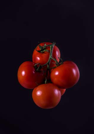 Red grapola tomato levitating on a dark background