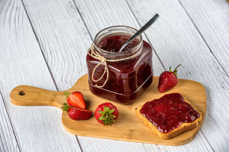 Homemade strawberry jam in a glass jar and spread over a toast bread with fresh strawberries at a cutting board on a white wooden background. Rustic style.