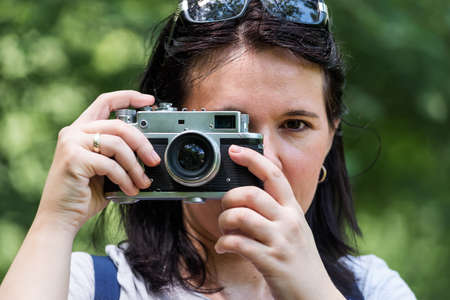Woman taking photo at park outdoor with copy space. Beautiful woman tourist photographer with vintage camera. lady photographer, female Portrait. Stock Photo