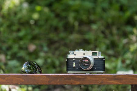 Spring time mood still life: vintage rangefinder camera and sunglasses laying on bencht, selective focus with background bokeh Stock Photo