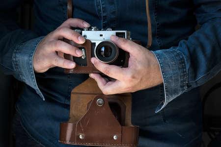 Men in jeans shirt holding an old rangefinder film camera camera