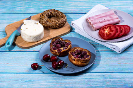 Breakfast served at blue wooden table with juice, ham, pecorino cheese, tomato, corn bread pretzel and sweet cherry pie. Continental delicious healthy breakfast table Stock Photo - 151267587