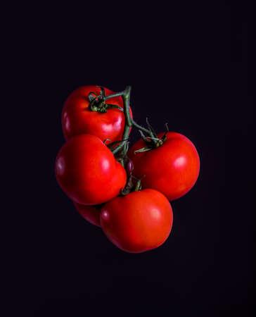 Red grapola tomato levitating on a dark background. Standard-Bild