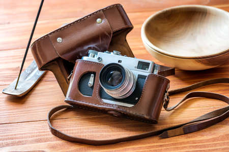 Vintage photo camera in leather case, incense stick and a wooden bowl on a rustic wooden table. Vintage rustic background.