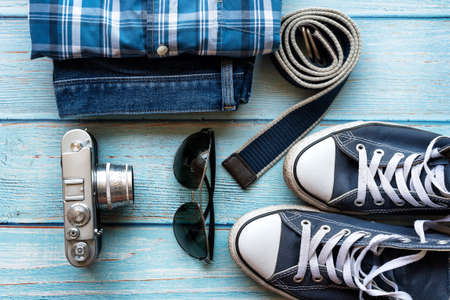 Set of men's clothing and accessories, flat lay. Hipster concept. Men's casual outfits, blue sneakers, blue jean, sunglasses old camera, blue canvas belt - top view. Stock Photo