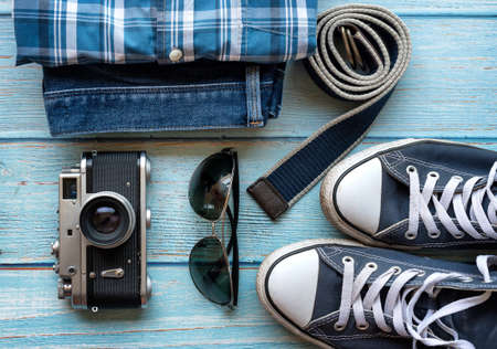 Set of men's clothing and accessories, flat lay. Hipster concept. Men's casual outfits, blue sneakers, blue jean, sunglasses old camera, blue canvas belt - top view. Standard-Bild