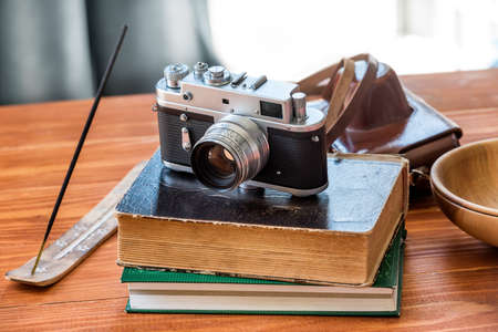 Old vintage camera and books with incense stick at old wooden table in the garden