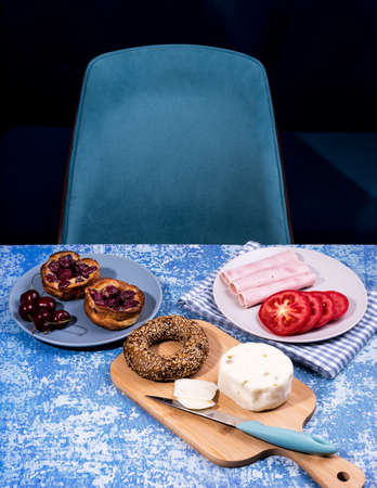 Breakfast served at blue wooden table with juice, ham, pecorino cheese, tomato, corn bread pretzel and sweet cherry pie. Continental delicious healthy breakfast table Stock Photo