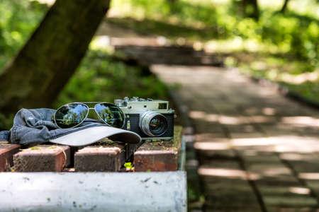 Vintage Phototographer Accesories on a bench un the park. Rangefinder old camera, sunglasses and a baseball hat