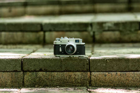 Vintage Photo camera at the city stone stairs. Rangefinder old camera at the stone step, selective focus
