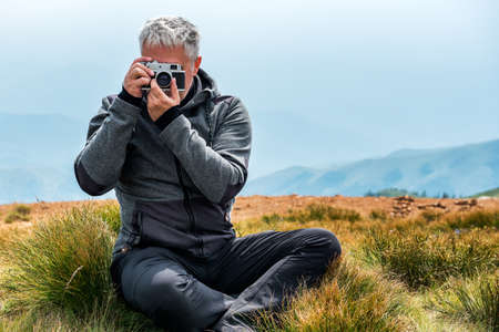 Photographer with old analog camera at a Mountain top. Mountain landscape view. Mountain layers landscape. Meadows and mountains landscape. Blue mountains layers landscape. Top of the Mountains