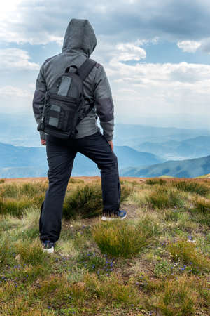 Man with backpack at a Mountain top. Mountain landscape view. Mountain layers landscape. Meadows and mountains landscape. Blue mountains layers landscape. Top of the Mountains