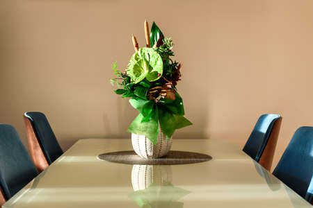 Green Anthurium andraeanum flower setup in a vase on glass dininig table in living room. Air purifying plants in the home decor Stock Photo